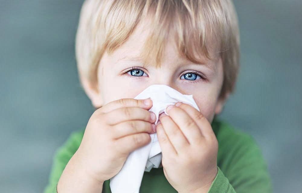 little boy wiping nose