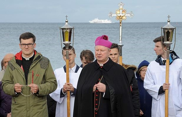 Priest leading rosary on baltic beach