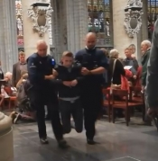 Police carry Catholic hero out of Brussels Cathedral